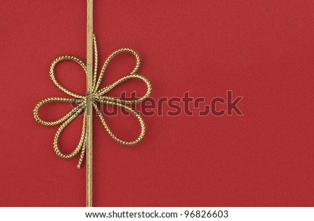 Single festive gold ribbon bow on red background with room for your text - stock photo