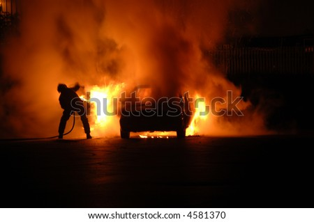 Single fire fighter struggles alone to put out blazing car fire, moving trying to dodge the heat and at the same time aim the hose - stock photo