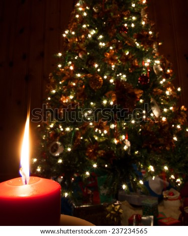 Single flame from a candle in front of a Christmas tree