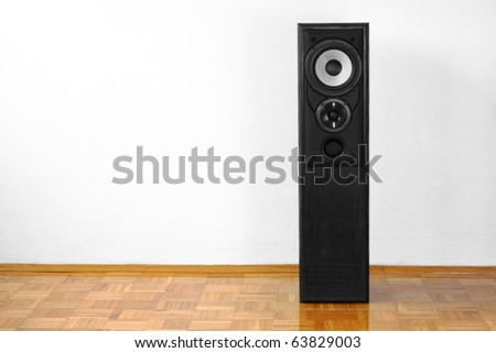 Single floor-standing loudspeaker on hardwood against white wall - stock photo