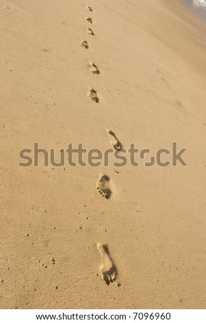 Single footsteps on the sand - stock photo