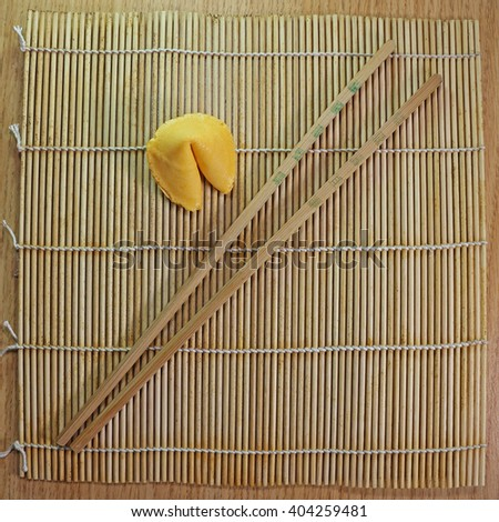 Single fortune cookie on bamboo mat chopsticks natural colors square - stock photo