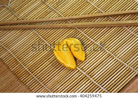 Single fortune cookie on bamboo mat with natural wood chopsticks - stock photo