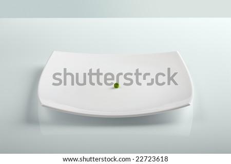 Single fresh green pea on white plate. - stock photo