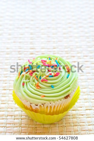 Single Fresh vanilla cupcake lime icing and sprinkles on woven straw background - stock photo