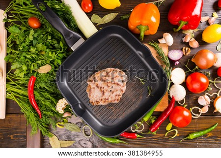 Single fried pork chop in middle of pan surrounded by fresh vegetables and herbs over wooden table - stock photo