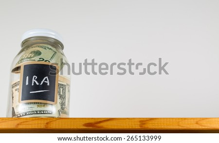 Single glass jar with chalk labels used for saving US dollar bills and notes for IRA retirement fund - stock photo