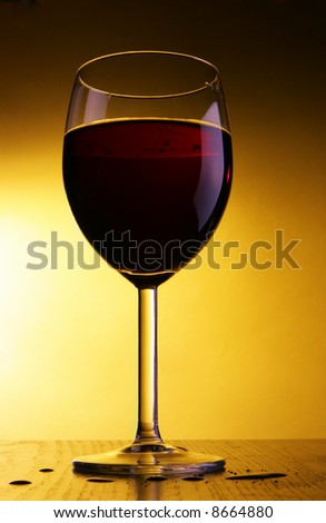 Single glass of red wine over yellow background