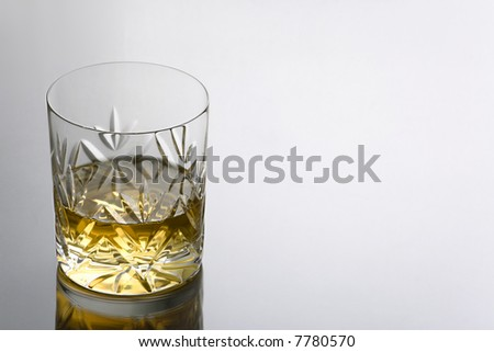 Single Glass of Whisky on a Reflective Surface with Copy Space - stock photo