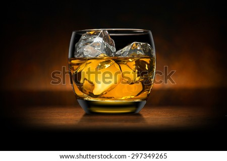 Single glass of whisky whiskey bourbon on ice on top of a wood bar table and wooden background - stock photo