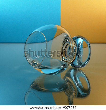 Single glass with blue yellow background. - stock photo