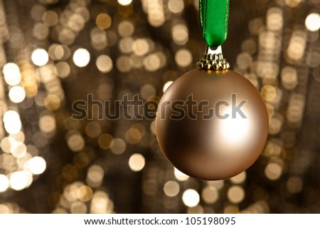 Single gold Christmas bauble in front of a gold glitter background for Christmas issues or other decoration issues - stock photo