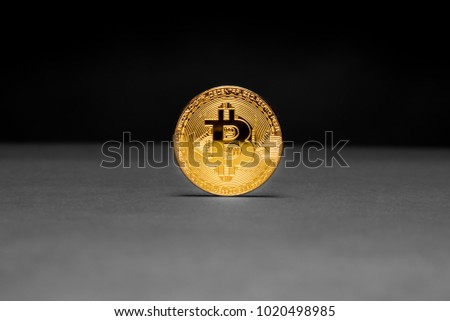 Single golden Bitcoin on black and grey background