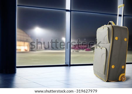 single gray suitcase and blue floor of airport and window  - stock photo
