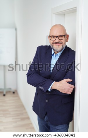 Single grinning mature bearded man with eyeglasses and bald head leaning against wall with folded arms and copy space - stock photo