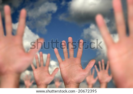 single hand in front of several hands on cloudy background - stock photo
