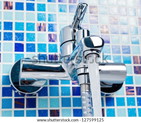 Single handle wall-mount bathroom sink tap with running water - stock photo