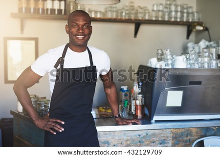 Single handsome young confident male coffee house owner with white shirt and black apron at counter with hand on hip - stock photo