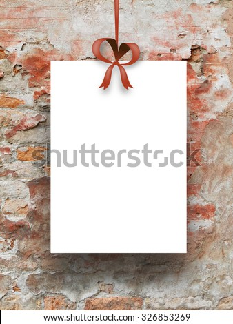Single hanged paper sheet frame with ribbon on red scratched wall background - stock photo