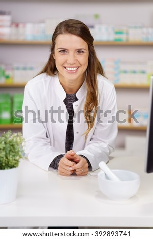 Single happy beautiful young female pharmacist in white lab coat leaning on table with bowl and pestle in pharmacy