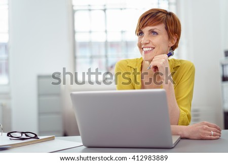 Single happy young woman in short red hair at laptop with big smile while looking out to side in office with copy space - stock photo