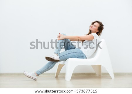 single happy young woman sitting on a white chair in an empty room, thinking on something - stock photo