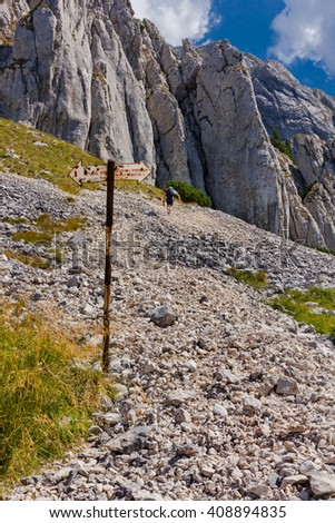 Single hiker on the gravel trail in the Piatra Craiului mountains, in the Southern Carpathians in Romania - stock photo