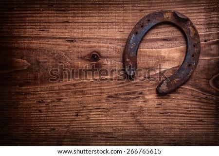 single horseshoe on vintage wooden board  - stock photo