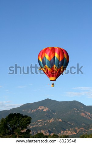 Single hot air balloon with the Rocky Mountains as backdrop - stock photo
