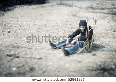 Single human in gas mask sitting in the desert near the dead plant. Concept of the futuristic environmental disaster. Shallow depth of field due to the tilt/shift lens for movie effect - stock photo