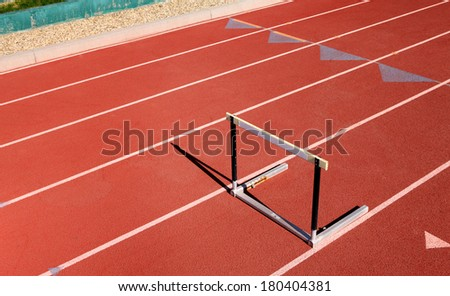 Single hurdle on red sports track - stock photo