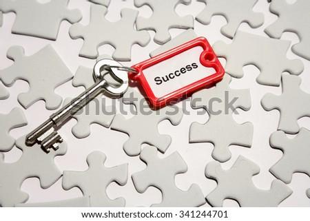 Single key on jigsaw puzzle pieces - stock photo