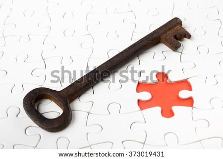 Single key resting on jigsaw puzzle - stock photo