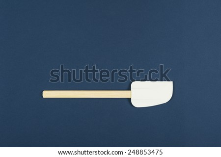 Single kitchen spatula used for baking and cooking in the preparation of food on a blue background with copyspace, overhead view - stock photo