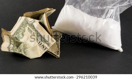 Single large bag of the cocaine drug and crumpled American dollars - stock photo