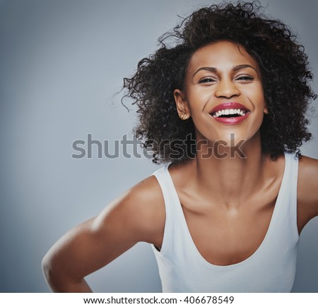 Single laughing young Black adult female in sleeveless undershirt with happy expression leaning forward over gray background and copy space - stock photo