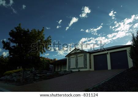 Single level house with bright sky - stock photo
