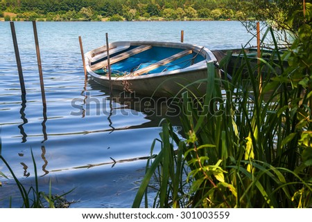 Single little boat floating beetween some rods and reed in the foreground on a lake - stock photo