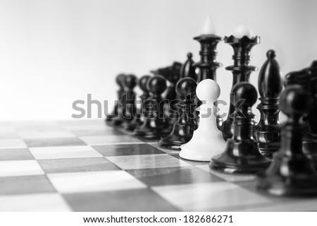 Single little pawn among many enemies. - stock photo
