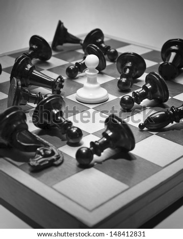 Single little pawn defeating many enemies. - stock photo