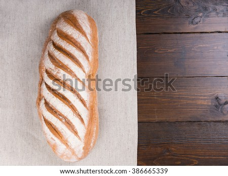 Single loaf of leavened durum flour bread on bakery paper over dark wood table from first person perspective - stock photo