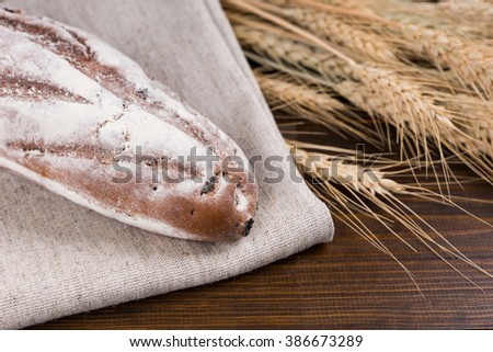 Single loaf of rye bread baguette on brown cloth next to dried wheat stalks over wooden table - stock photo