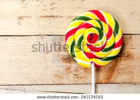 Single lollipop on wooden background. - stock photo