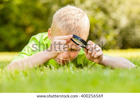 Single male child in blond hair and green shirt laying down on grass while looking at something and holding a black magnifying glass outdoors - stock photo