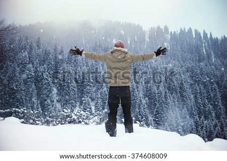 Single male standing on top of the snow hill facing mountains with arms wide open to the sky - stock photo