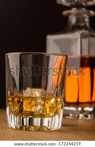 Single malt whiskey on the rocks with a carafe in background - stock photo