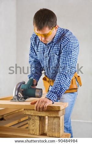 single man cuts the board - stock photo