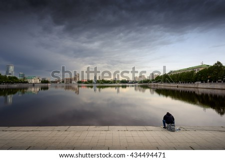 Single man sits and fishes in the City Pond in Yekaterinburg. The vast stretch of water is a key tourist attraction for people visiting the Ural mountain city in Russia. - stock photo