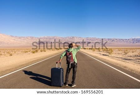 Single man walking alone into the desert - stock photo