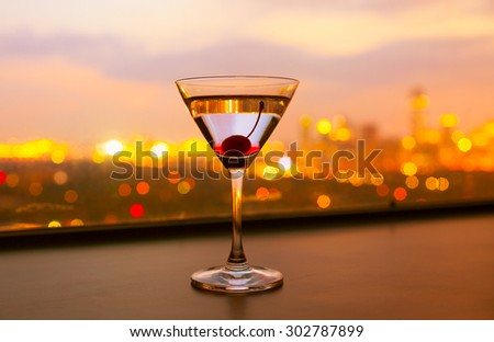 Single martini glass with city views.  - stock photo